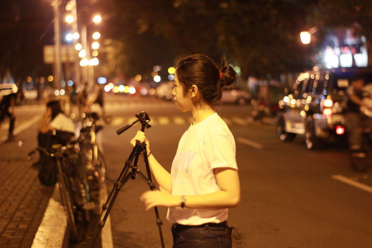 Young Woman Holding Tripod On Illuminated Street At Night