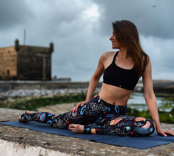 Woman Practicing Yoga On Exercising Mat Over Retaining Wall Against Sky