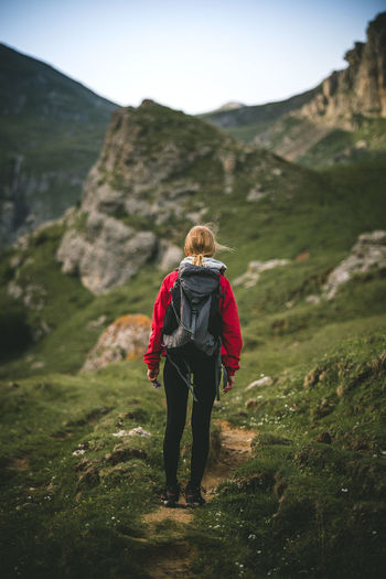 Adventure Backpack Beauty In Nature Day Full Length Grass Green Color Healthy Lifestyle Hiker Hiking Leisure Activity Lifestyles Mountain Mountain Range Nature One Person Outdoors Real People Rear View Scenics Standing Walking Women Young Adult Young Women Be. Ready.