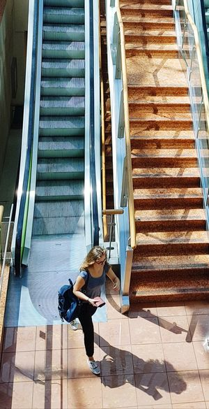 High angle view of woman walking on staircase of building