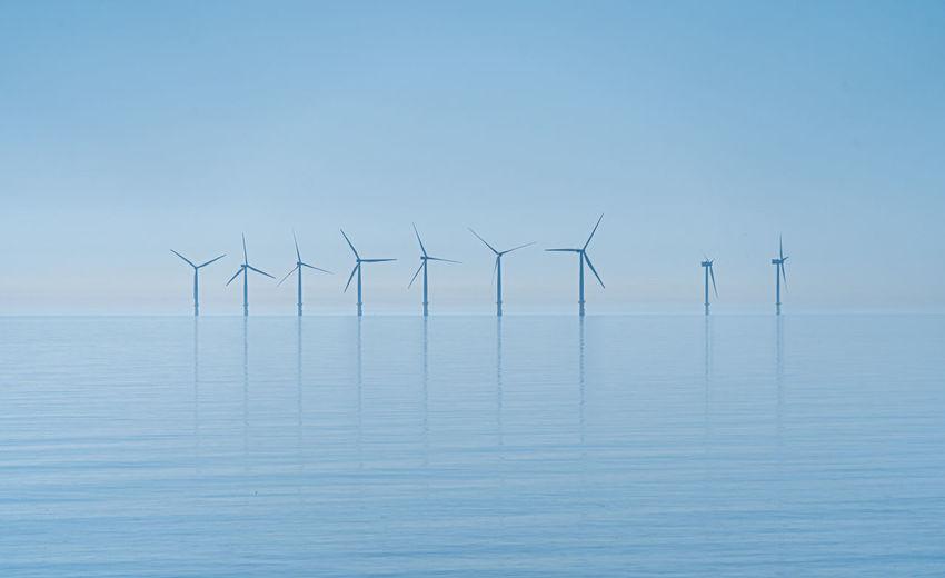 Wind turbines in sea against sky