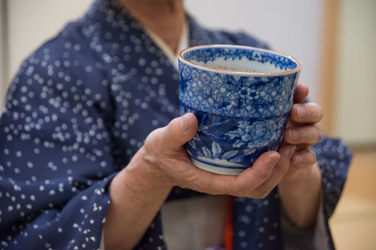 Midsection of person holding japanese tea cup