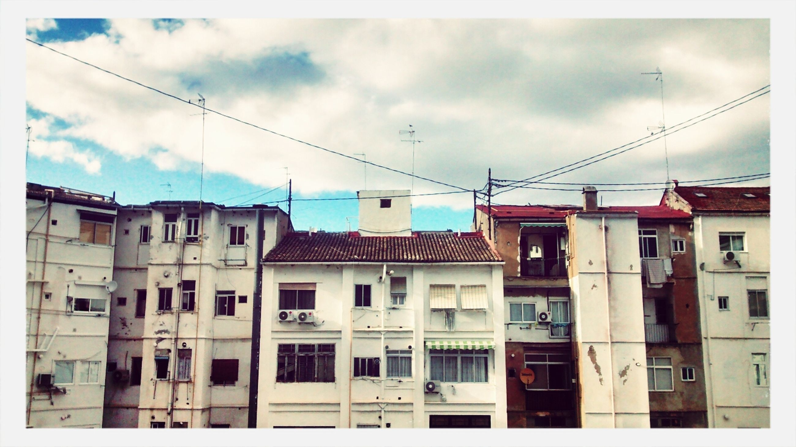 architecture, building exterior, built structure, low angle view, sky, power line, transfer print, cloud - sky, cable, auto post production filter, cloud, building, window, residential building, cloudy, residential structure, day, city, outdoors, no people