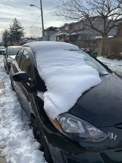 Snow covered car by building