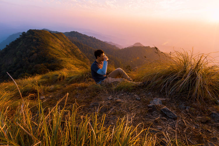 Side view of male hiker drinking while sitting on mountain against sky during sunset