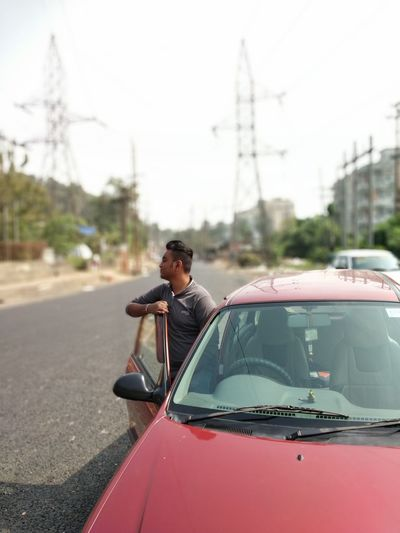 Man standing by car on road in city