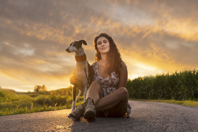 Portrait of woman with dog sitting on road against sky during sunset