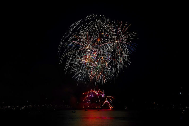 Arts Culture And Entertainment Blurred Motion Celebration Copy Space Dark Event Exploding Firework Firework - Man Made Object Firework Display Glowing Illuminated Light Long Exposure Motion Multi Colored Nature Night No People Sky Water