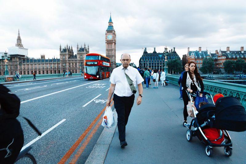 People Walking On Westminster Bridge By Big Ben Against Cloudy Sky