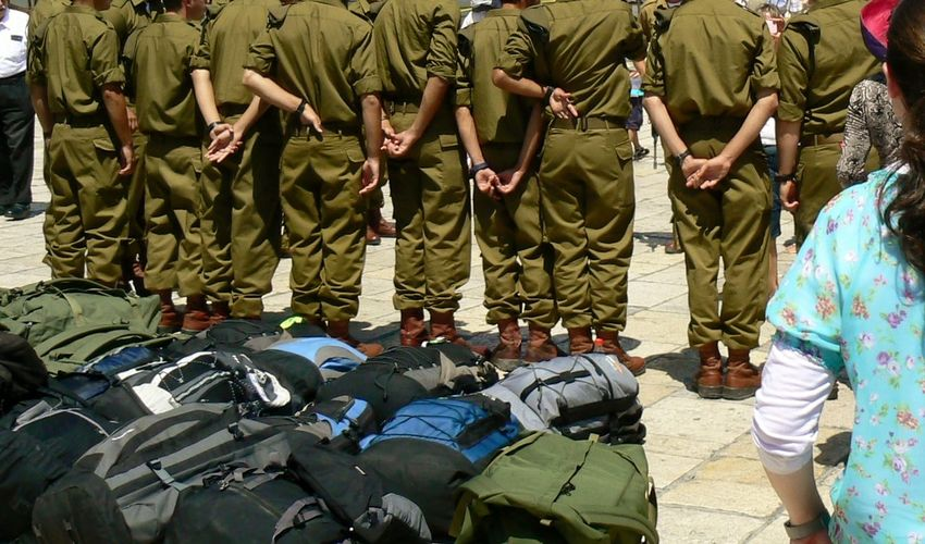 Rear View Of Soldiers Standing By Backpacks On Street
