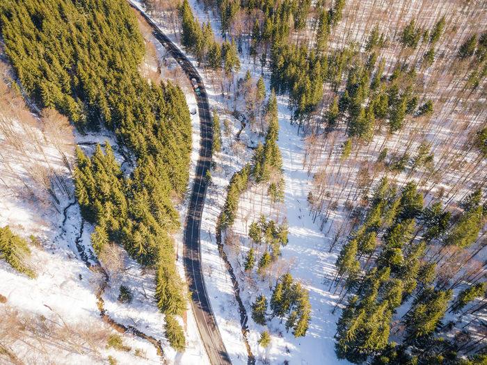Winding road from high mountain pass, in winter. aerial view by drone . romania