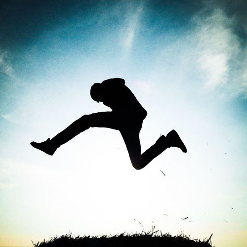 Low angle view of silhouette woman jumping against sky