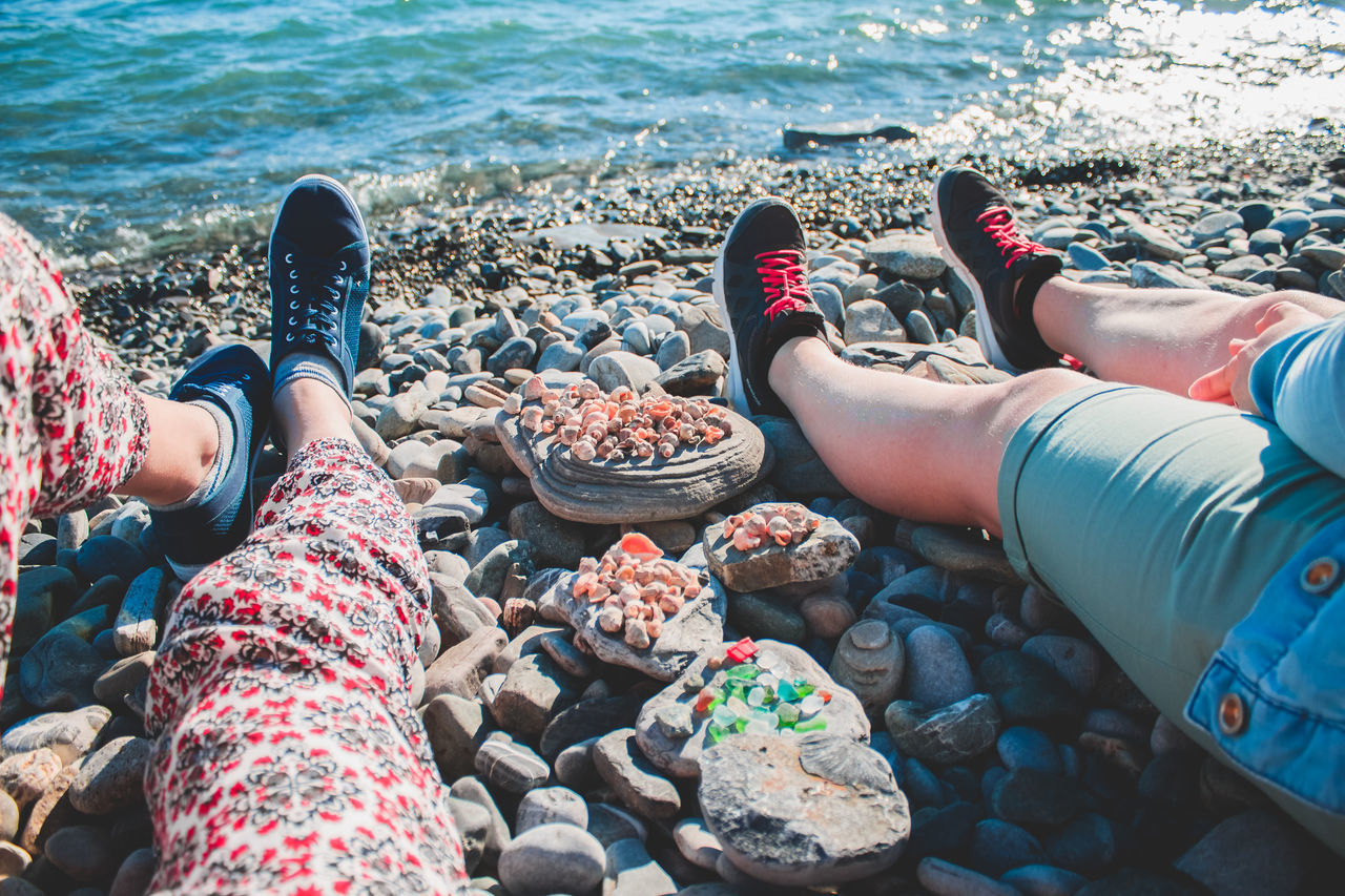 low section, human leg, real people, human foot, day, personal perspective, leisure activity, men, human body part, outdoors, lifestyles, water, beach, sunlight, vacations, pebble, shoe, high angle view, women, barefoot, nature, sand, standing, relaxation, sea
