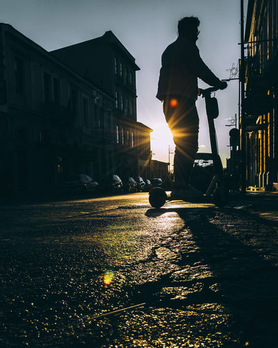 Silhouette man on street against sky during sunset