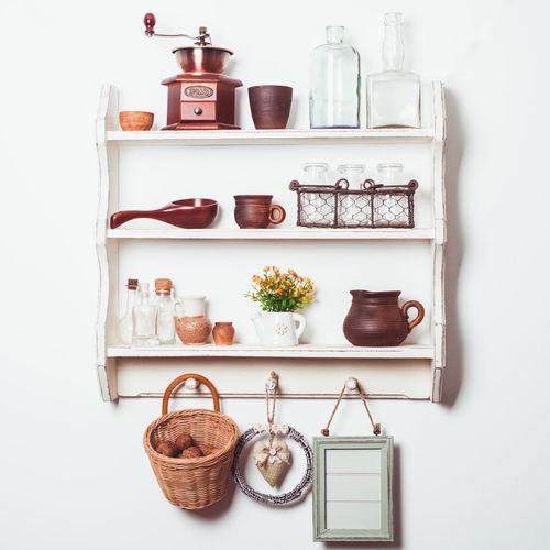 Close-up of wine bottles on shelf against white background