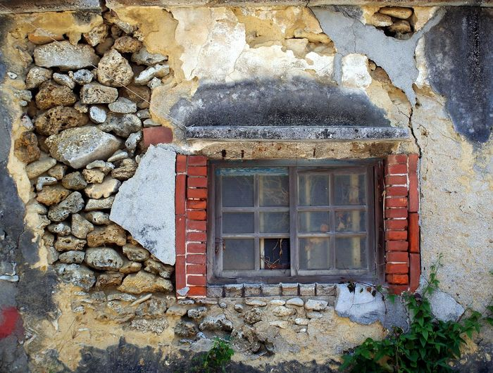 An old deserted house with walls made from rocks with wood frame window Built Structure Deserted Home Dilapidated House Old Building  Old Ruin Plaster Rock Wall Rural Building Window Wooden Window