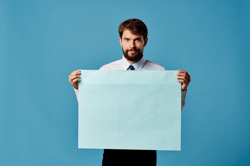 Portrait of man standing against blue background