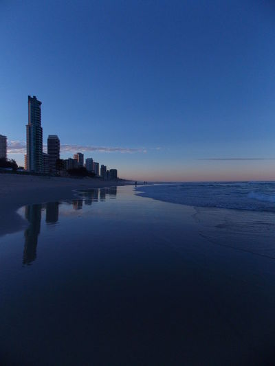 Buildings Reflection On Wet Shore At Surfers Paradise Against Sky