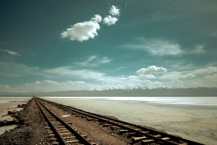 Railway tracks cross the desert China View Cloud - Sky Desert Future Lake Land Landscape Mountain Outdoors Path Railway Track Saline Lake Sand Scenics Sky The Way Forward Train Tracks Travel Destinations Way