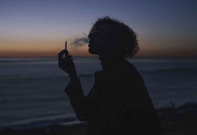 Water Sky Sea Sunset One Person Beach Real People Silhouette Holding Lifestyles Leisure Activity Nature Land Cigarette  Smoking Issues Activity Waist Up Outdoors