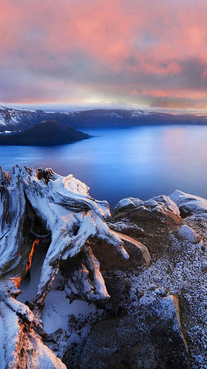 Scenic View Of Frost On Landscape Surrounding Calm Sea At Sunset