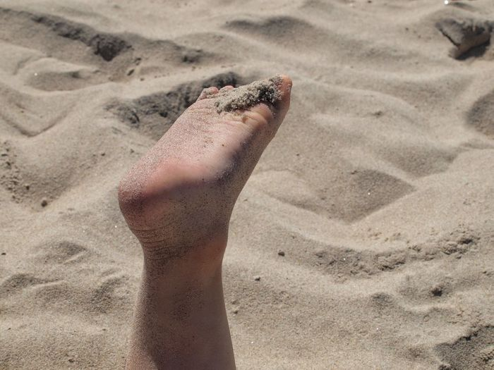 Low section of woman on sand