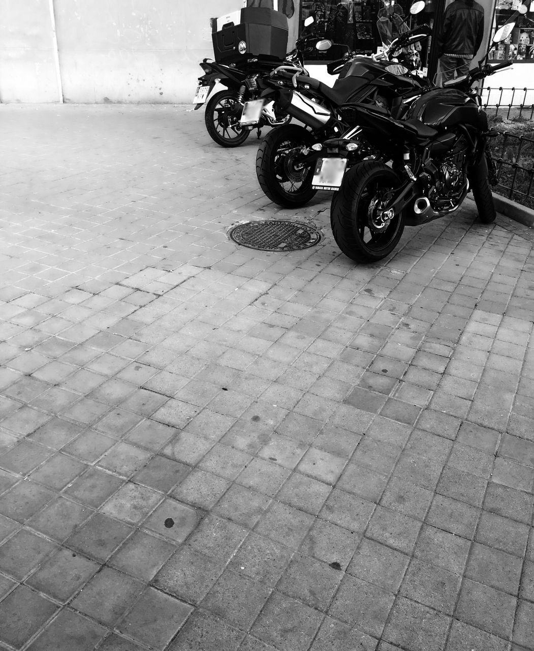 transportation, mode of transportation, city, motorcycle, land vehicle, street, day, outdoors, wheel, no people, travel, footpath, stationary, architecture, side view, road, scooter, tiled floor, paving stone