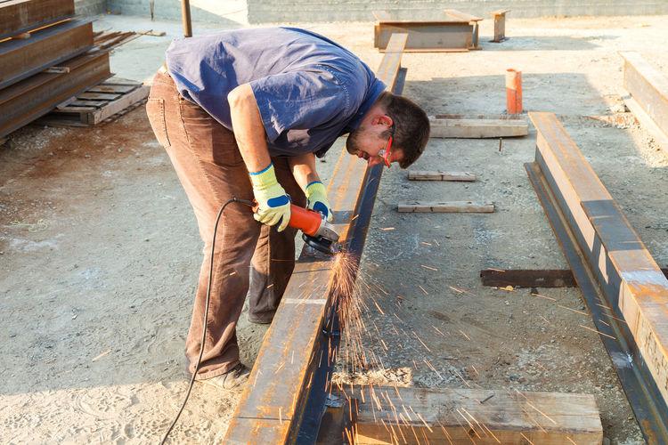Full length of welder welding metal at construction site