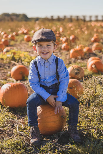 Portrait of smiling boy sitting on pumpkin at field
