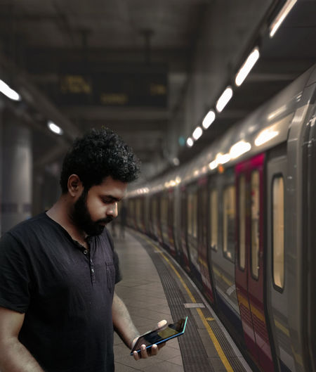 a cool guy standing  at metro station