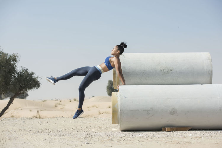 Black African American athletic woman jumps over and leaps from construction pipes wearing sports outfit in a parkour or extreme fitness competition. Athlete Athletics Black Woman Parkour And Free Running African American Woman Construction Pipes Day Desert Landscape Fitness Training Full Length Jumping Leaping One Person Outdoors People Real People Skills  Sky Young Adult Young Women