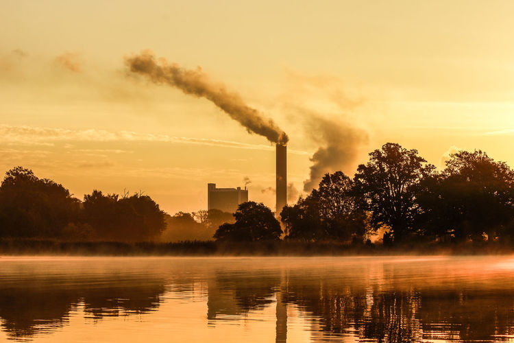 Air Pollution Architecture Atmospheric Built Structure Chimney Ecosystem  Emitting Environment Environmental Issues Factory Foggy Morning Fuel And Power Generation Industry Pollution Reflection Smoke Smoke - Physical Structure Smoke Stack Tree Water Waterfront