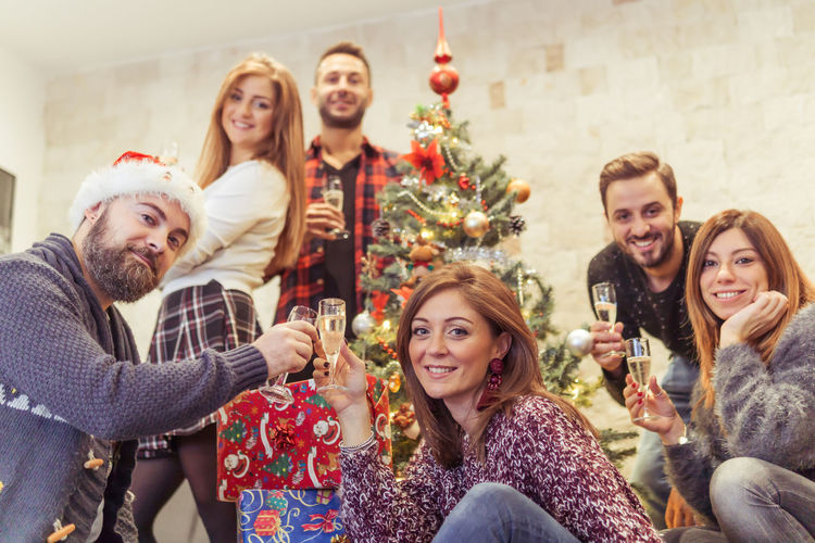 Happy and smiling friends toast under the christmas tree Holiday Moments Man Woman People Glass Christmas Ornament Celebratory Toast New Year's Eve Refreshment Event Friendship Drink Young Men Alcohol Holiday Group Of People Togetherness Adult Emotion Happiness Young Women Christmas Smiling Young Adult Celebration
