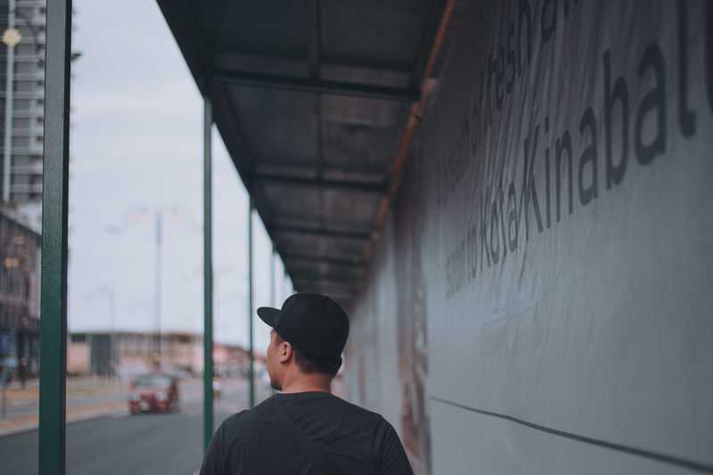 Rear view of man standing by wall in city