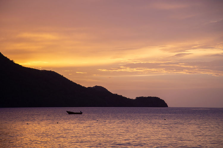 Scenic view of boat in sea against sky during sunset