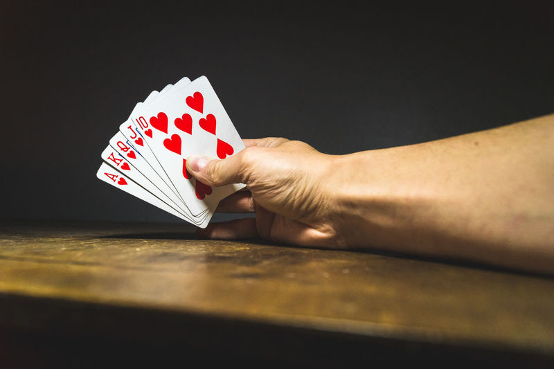 Cropped Image Of Hand Holding Cards On Table