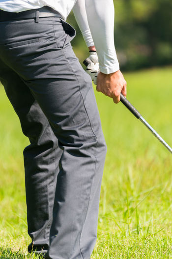 Low Section Of Man Playing Golf On Course
