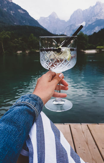 Personal perspective of woman holding glass with drink. lake, mountains in background.