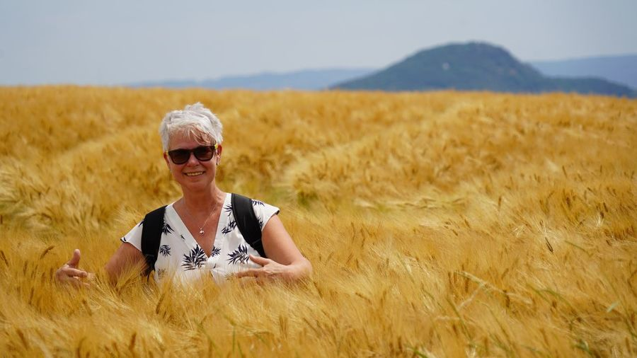 Woman wearing sunglasses on barley field against sky