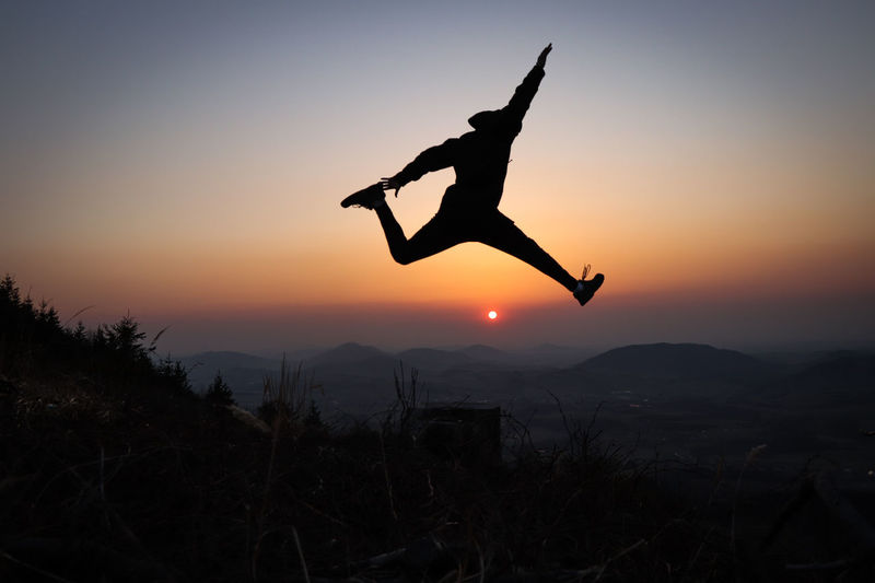 Silhouette man jumping on mountain against sky during sunset