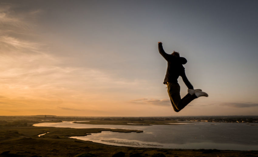 Silhouette man jumping over sea against sky
