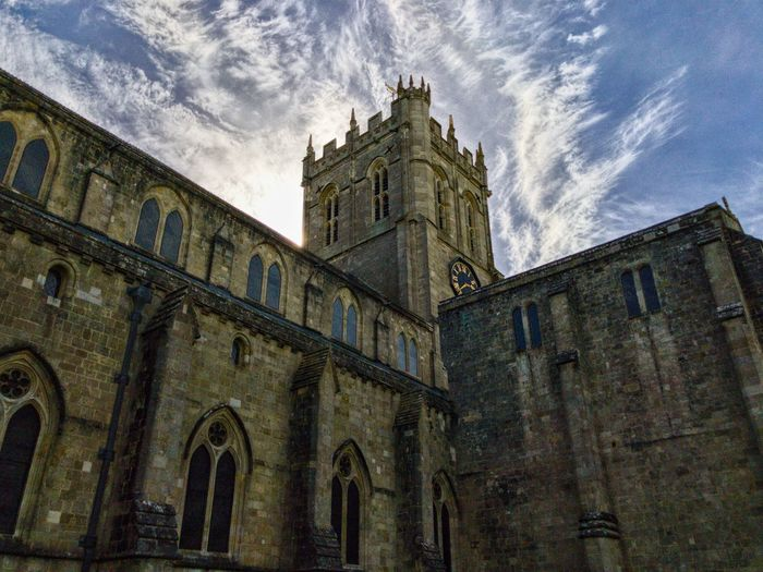 Low angle view of historic church against cloudy sky