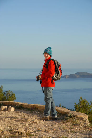 Woman hiking in winter Adult Adults Only Backpacking Beauty In Nature Blue Coast Day Female Full Length Hat Hiking Leisure Activity Nature One Person One Woman Only Outdoors People Sea Sky Standing Woman Woman Wearing A Hat Woman With Camera Young Adult