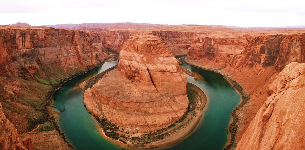 Colorado river flowing through horseshoe canyon against sky