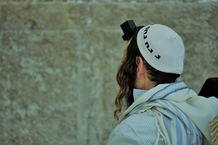 Rear view of man wearing hat and tefillin against wall