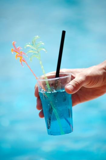 Close-up of hand holding drink against blue sky