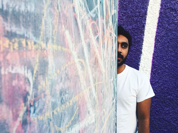 Cropped Image Of Man Standing Behind Graffiti Wall
