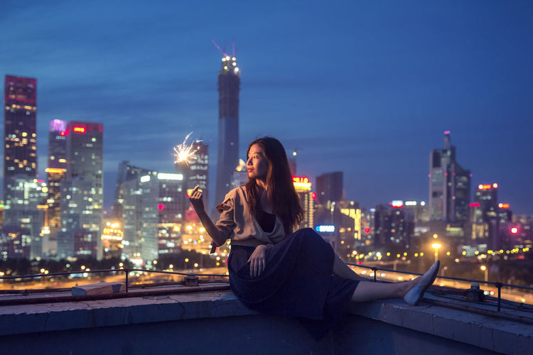 Woman using phone against buildings in city at night
