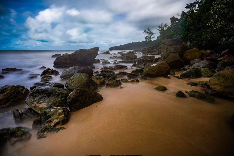 A scenic view of a long exposure shot at a stony beach in Kuching, Sarawak Cloud - Sky Water Sky Sea Beach Land Scenics - Nature Beauty In Nature Nature Rock - Object Tranquility Motion Environment Sand Rock Outdoors Solid Wave Travel Horizon Over Water