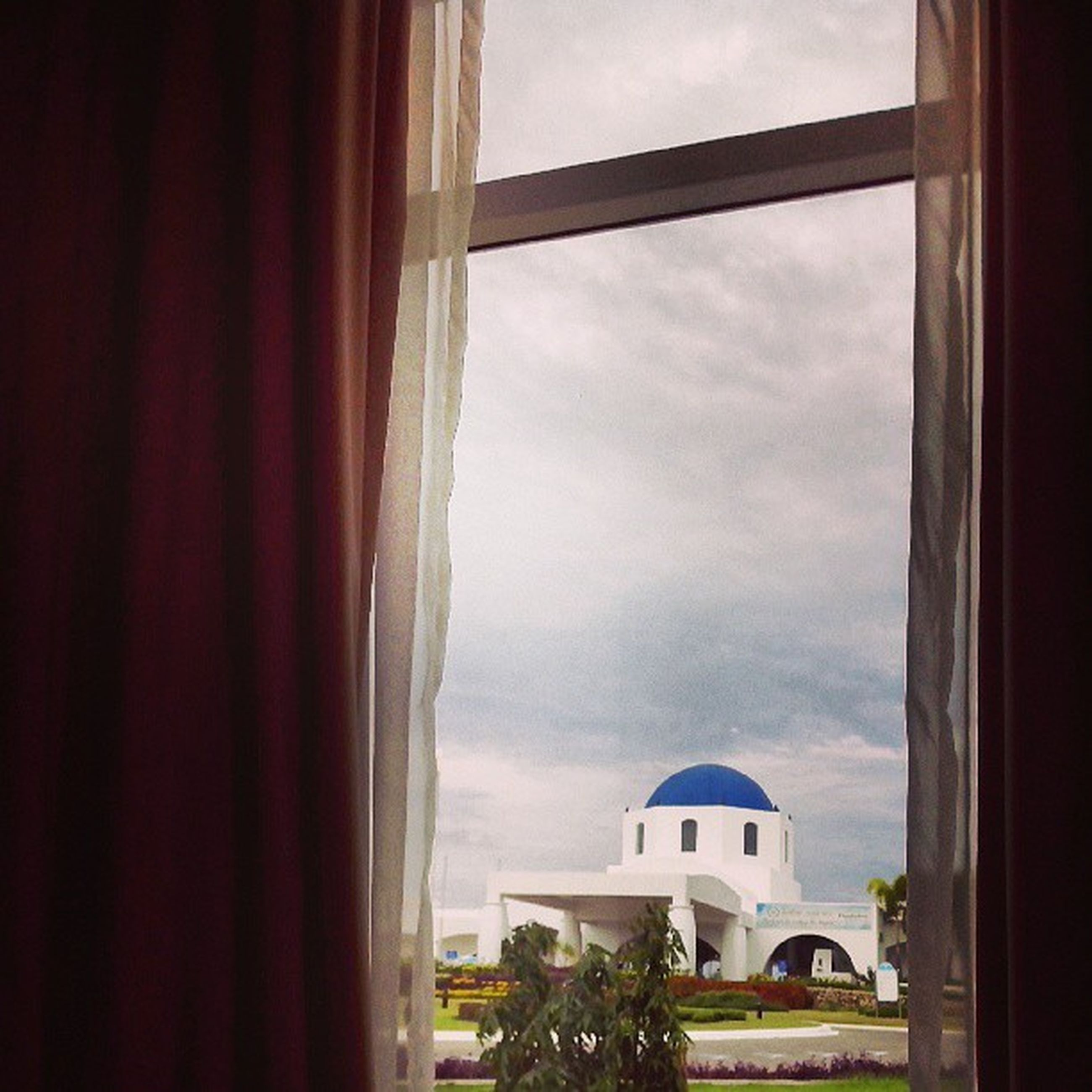architecture, window, built structure, building exterior, sky, house, indoors, cloud - sky, glass - material, cloud, transparent, residential structure, day, low angle view, church, building, cloudy, no people, tree, residential building